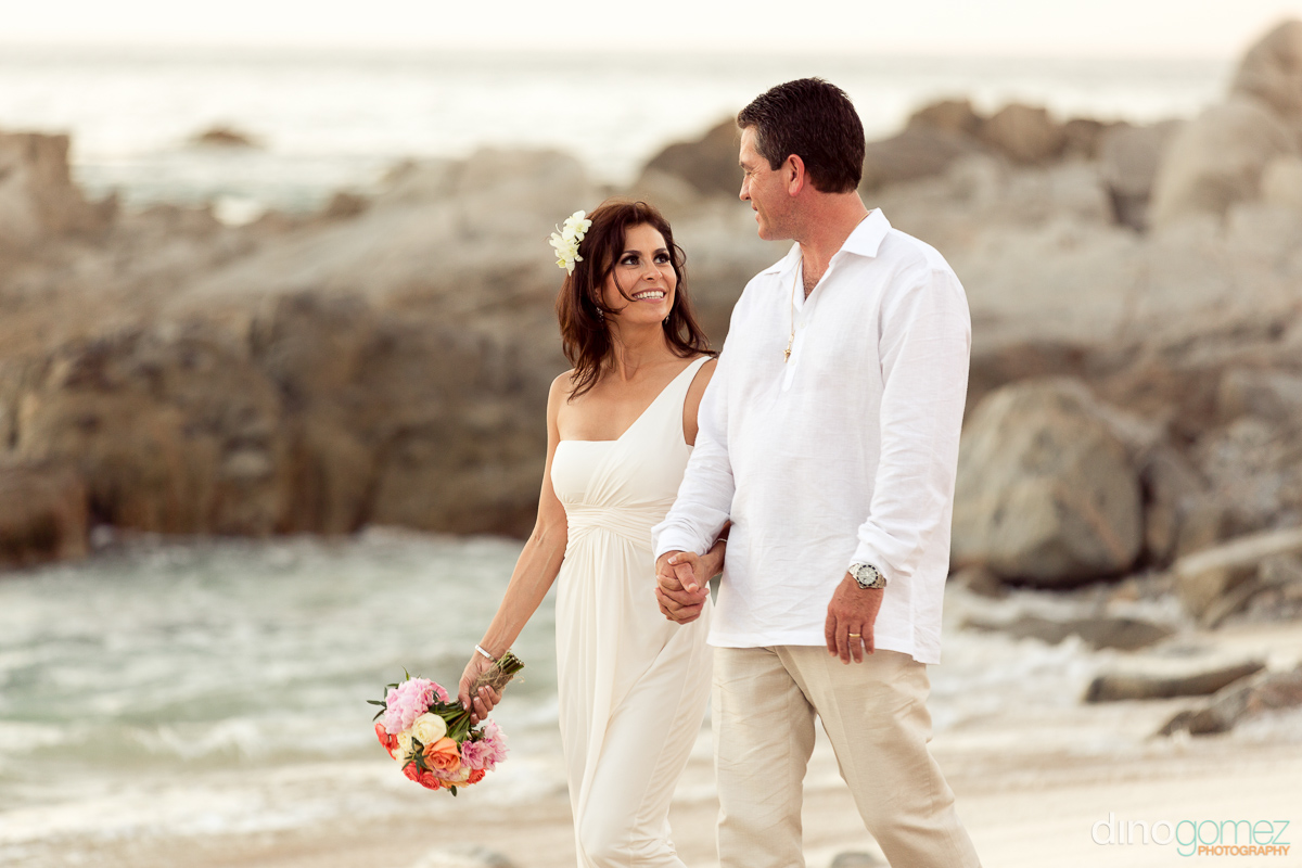 Bride and groom holding hands while walking on the beach in cabo san lucas