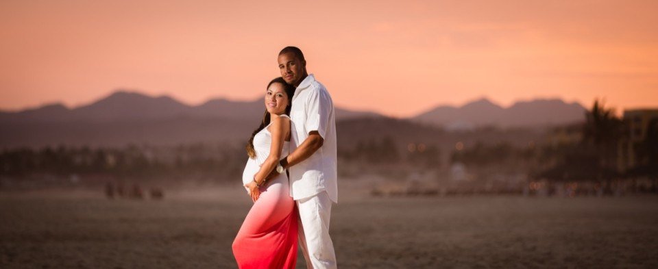 Pregnant mom and dad to be standing on beach at sunset in Mexico