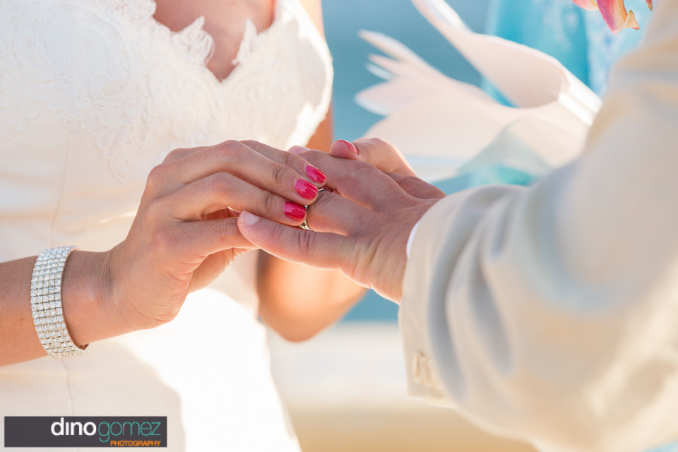 Great shot of the bride putting his ring on by destination wedding photographer Dino Gomez