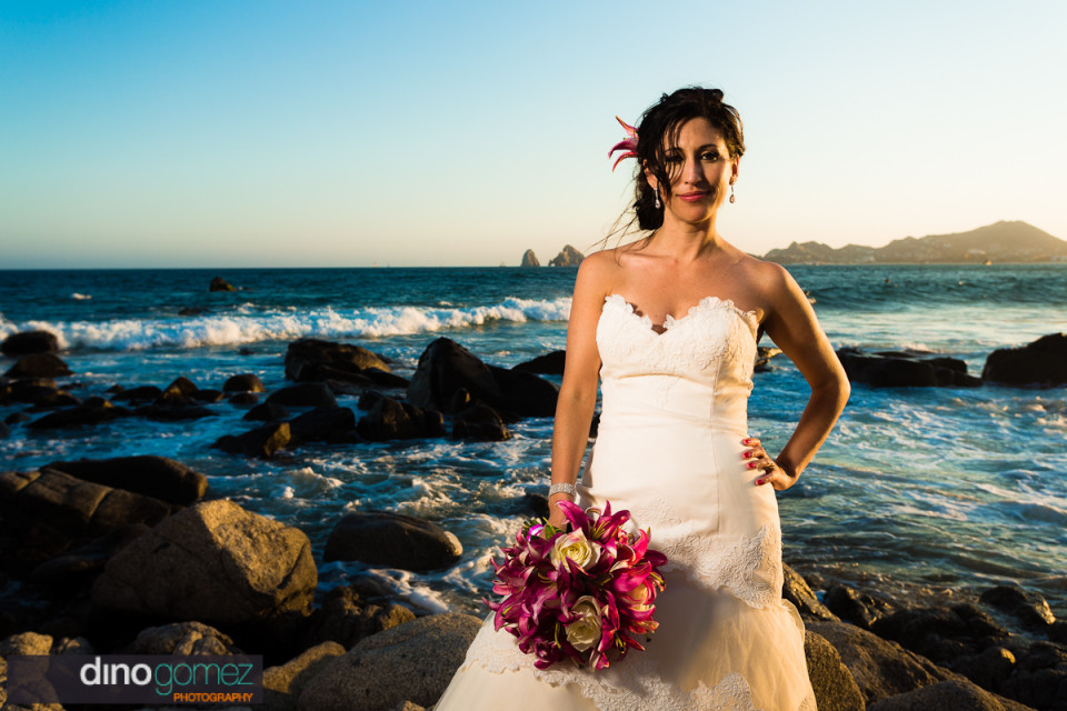 Bride standing on the rocks with the beautiful beach as the backdrop