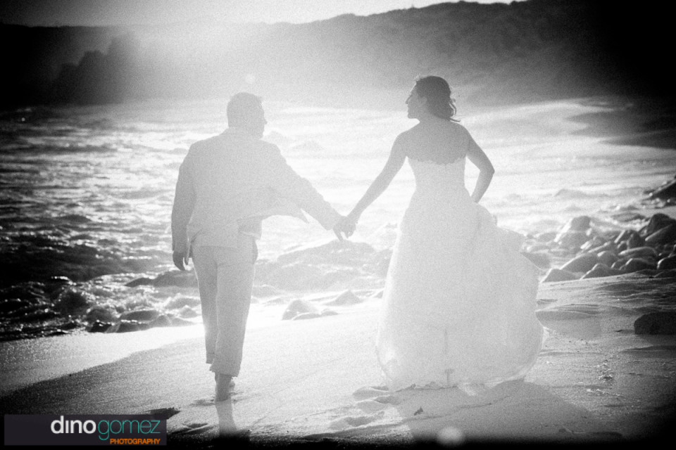 Bride and groom walking on beach by wedding photographer Dino Gomez