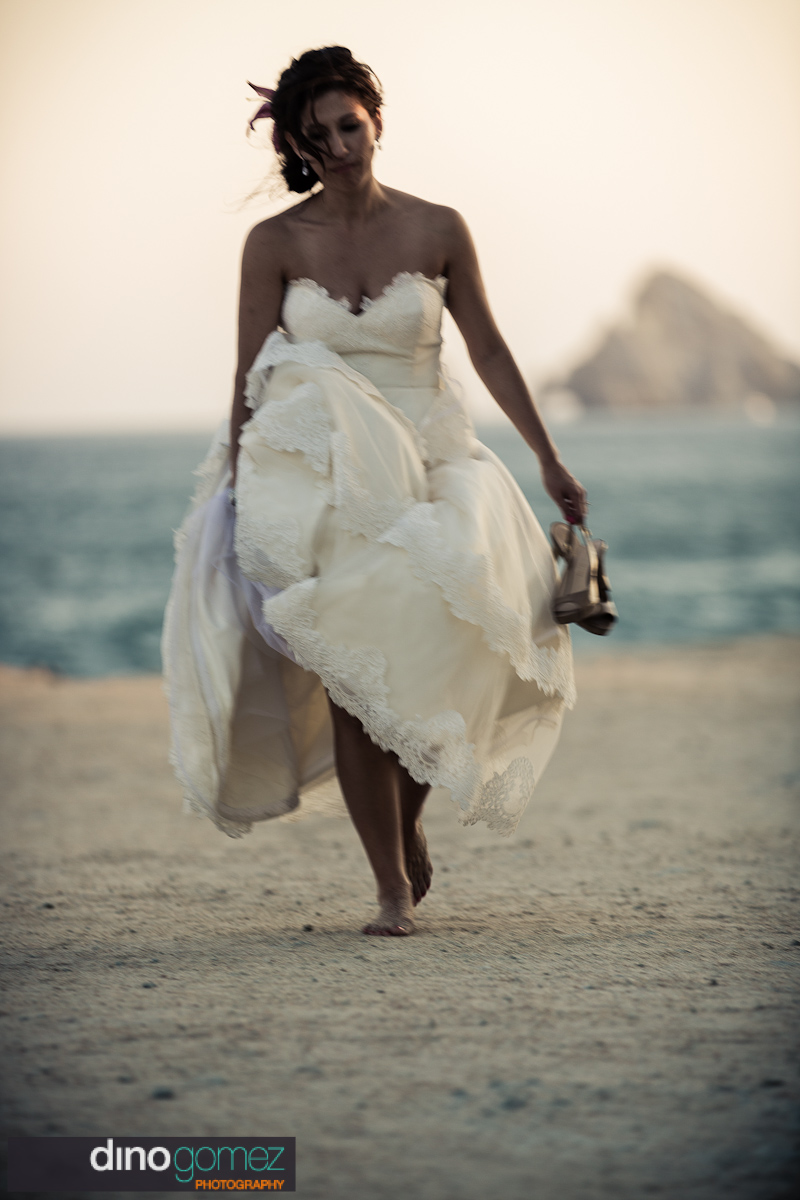 Bride enjoying a nice walk on the beach with her shoes in hand