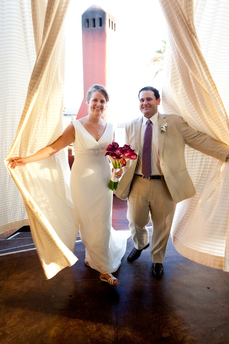 A newly married couple appear through a linen curtain, picture taken by Dino Gomez