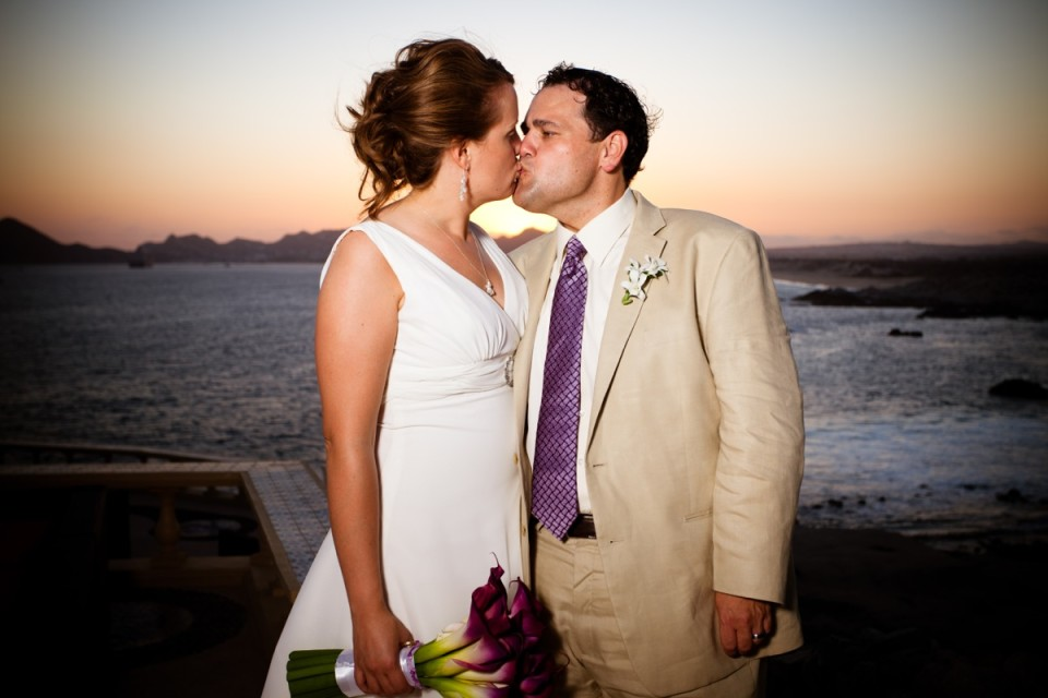 A loving couple share a kiss at their wedding as the sun sets behind them at their weddin in Cancun