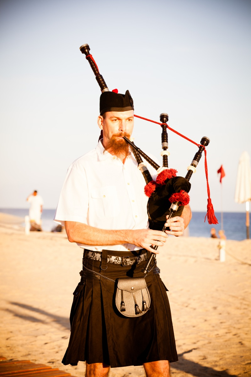 Wedding bagpiper playing melodies on the beach
