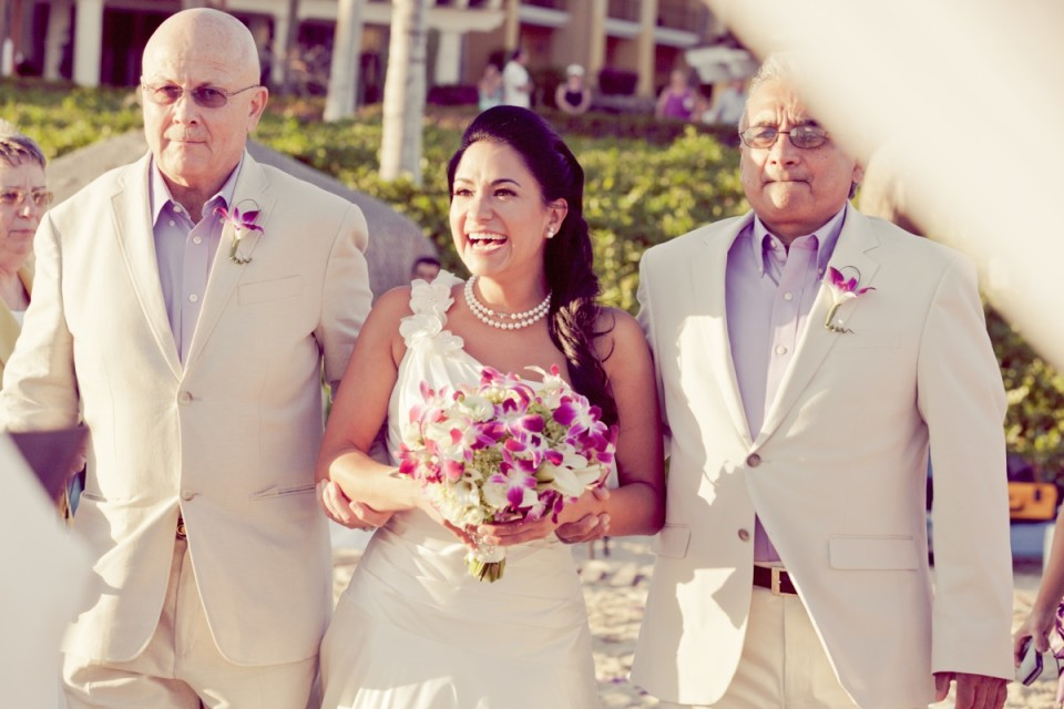 Bride walking down the aisle with two handsome gentlemen at her destination wedding