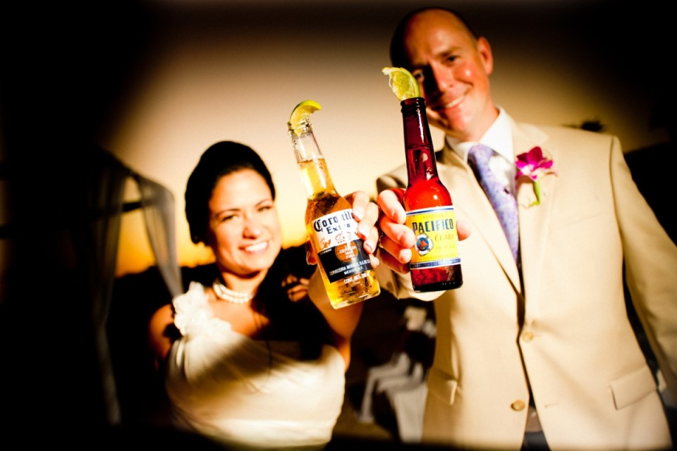 Bride and groom drinking beer together at destination wedding