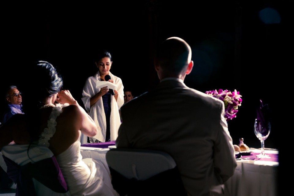 Woman giving wedding speech with back view of the bride and groom
