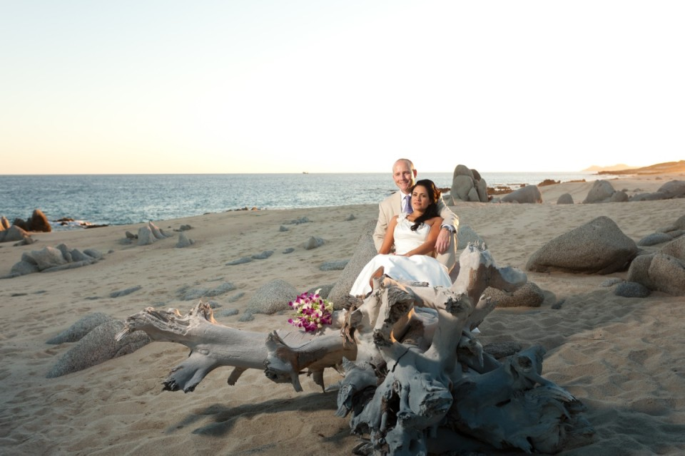 Bride and groom sitting on huge beach log
