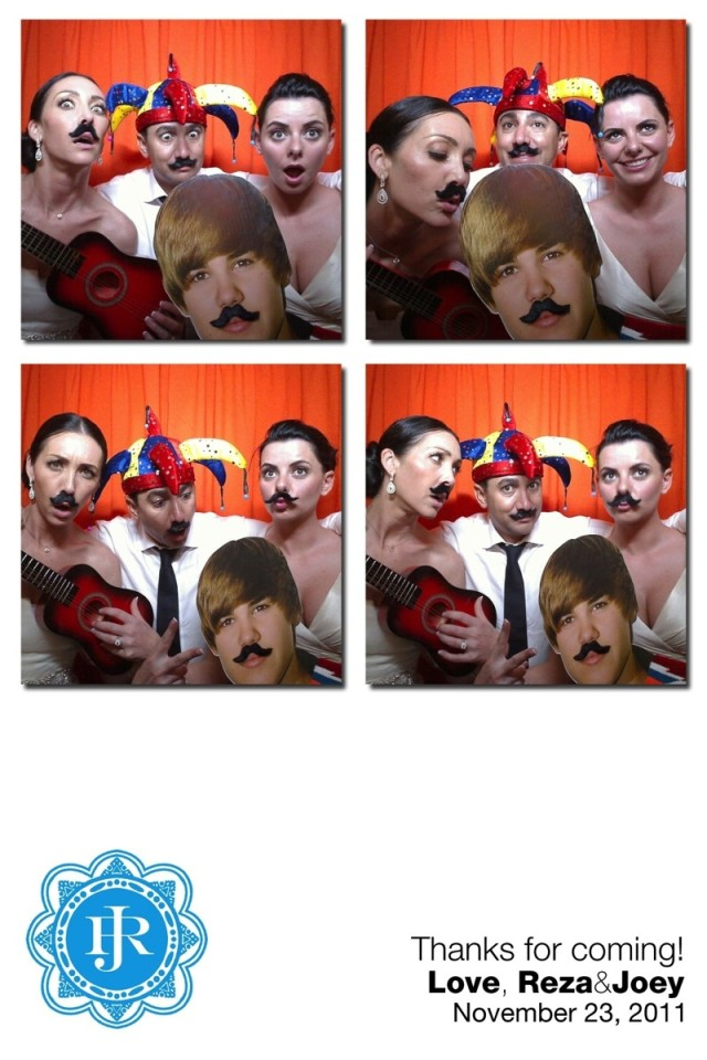 The bride, groom and a guest enjoy themselves with falses moustaches in a photobooth