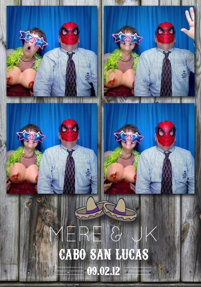 Wedding guests enjoy a photo booth by using props.
