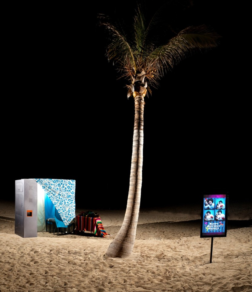 Night time image of a fun photo booth set up for a beach wedding