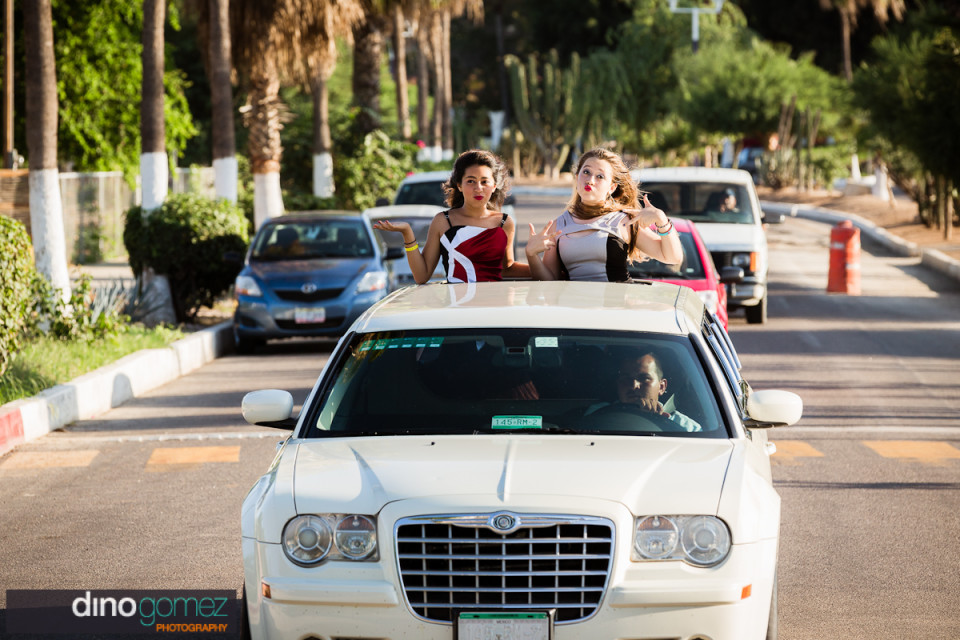 Happy teen cruises along in car with her BFF on her quinceañera