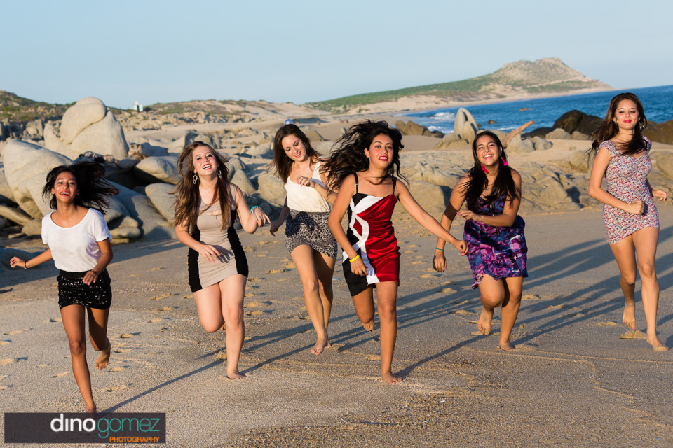 The Quinceañera and her beautiful friends running on the beach in Mexico