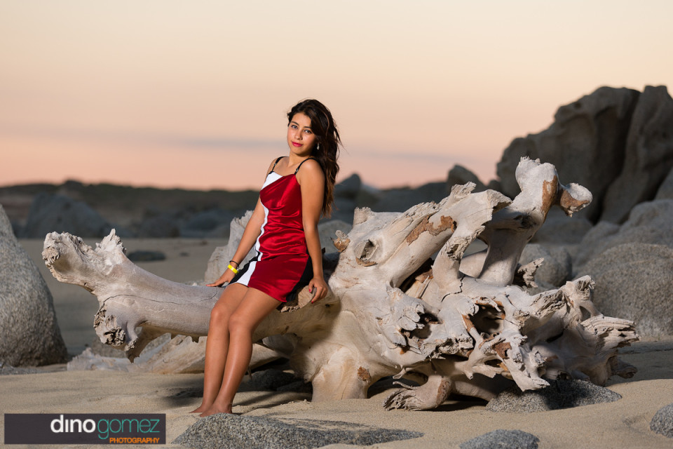 Birthday girl sitting on a beach log in a red and black dress with white details