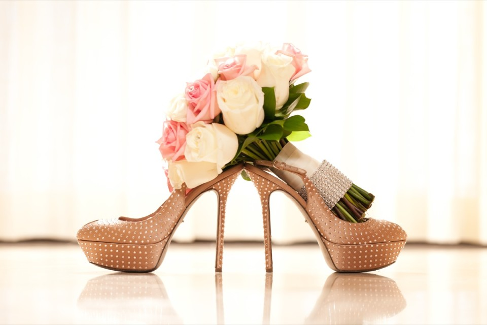 Bride's wedding shoes and bouquet of pink and white roses