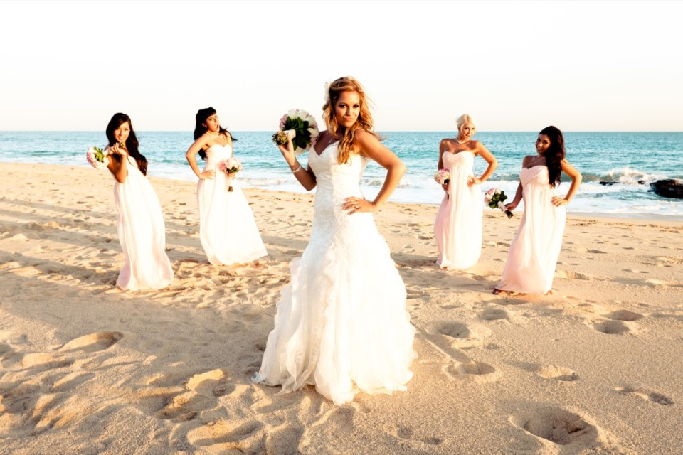 Destination beach wedding with bride and bridesmaid striking a fun pose on the sand