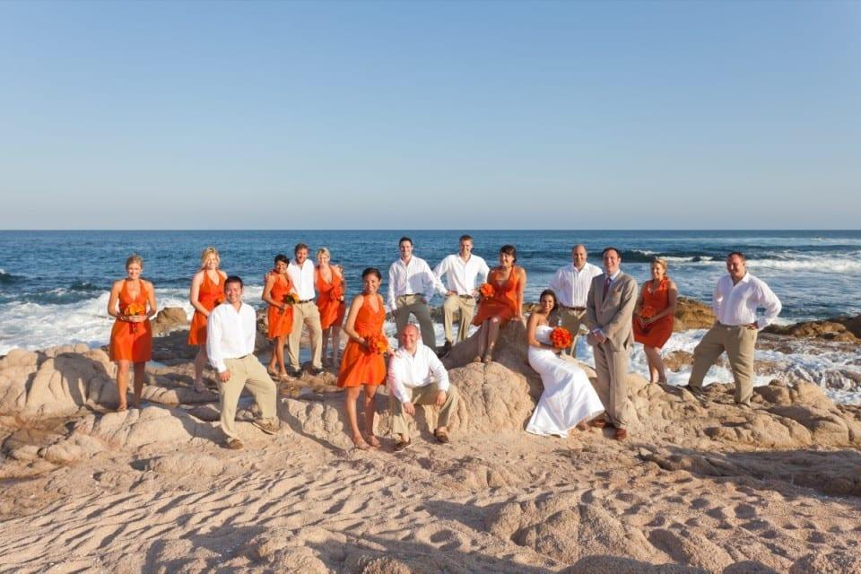 Beach wedding in Mexico featuring bridesmaids in bright orange dresses.