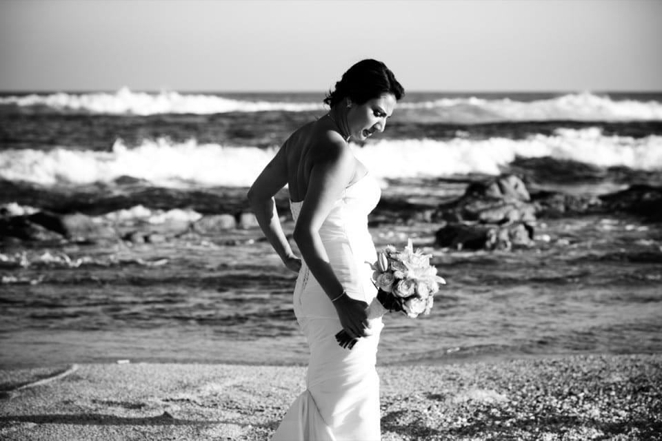 A bride looks down in contemplation at her beautiful bouquet whilst walking on the beach in Mexico