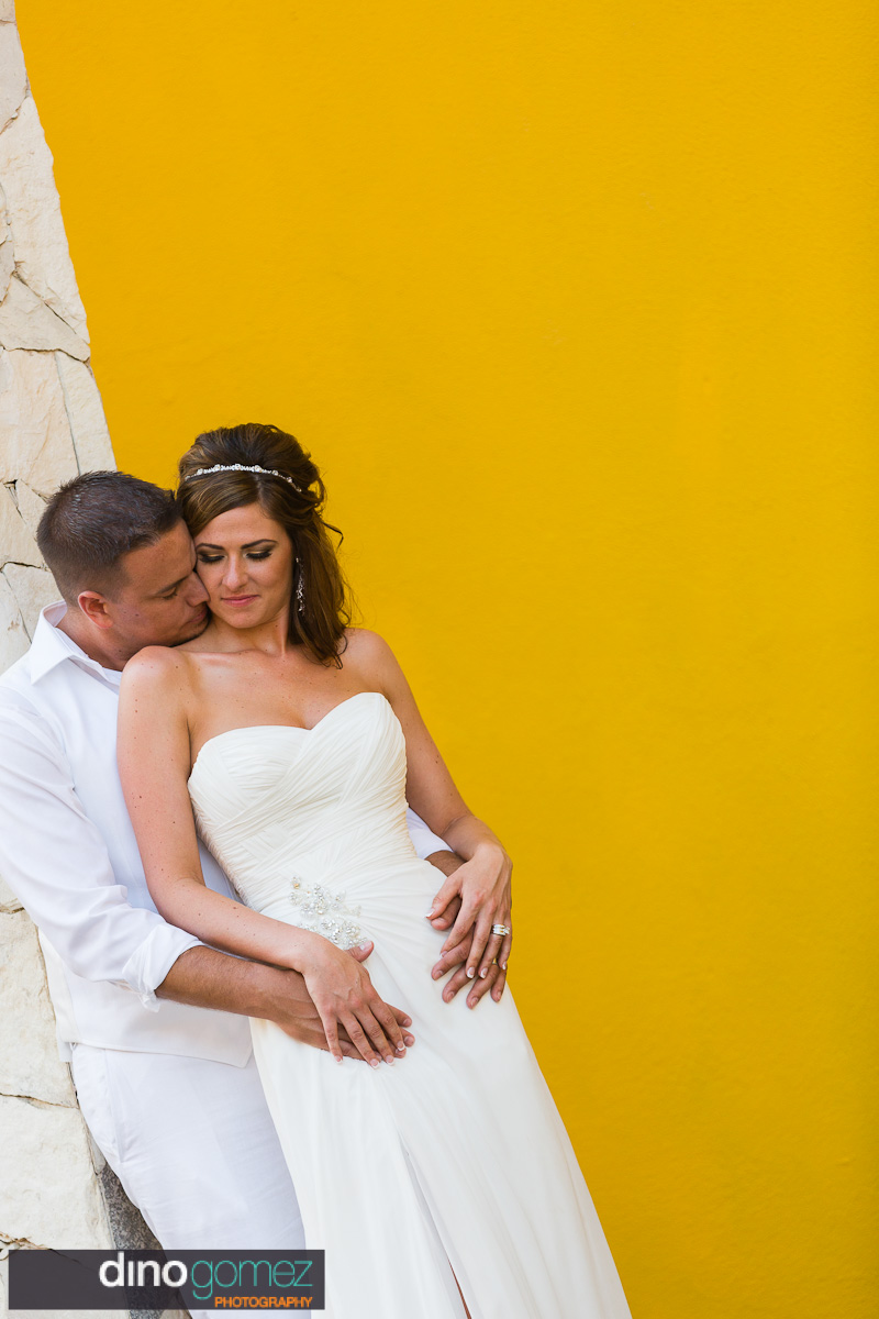 Bride and groom embrace on a stone wall next to a yellow coloured wall