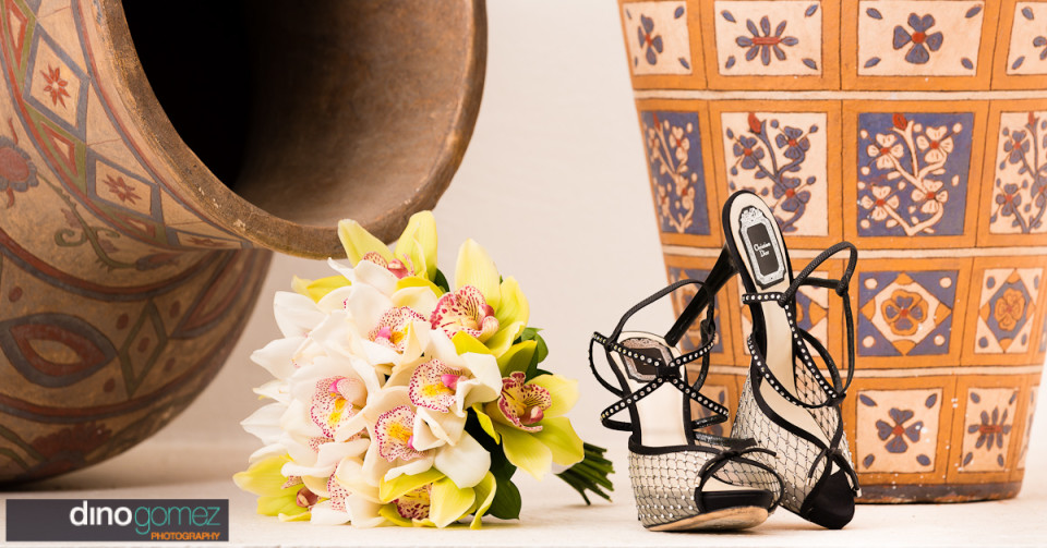 Wedding shoes and yellow and white bouquet shot by wedding photographer Dino Gomez