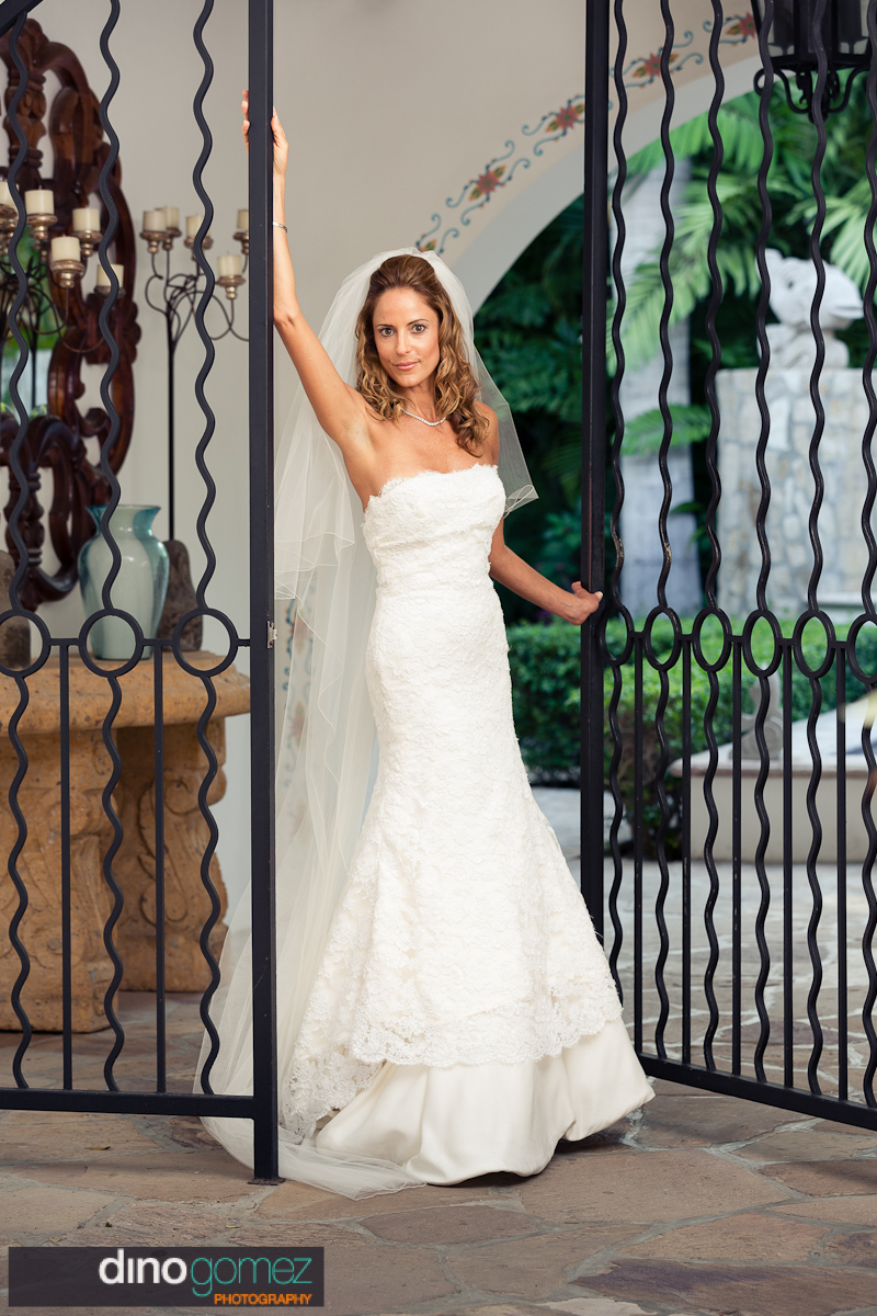 Full shot of the bride standing between a black iron gate