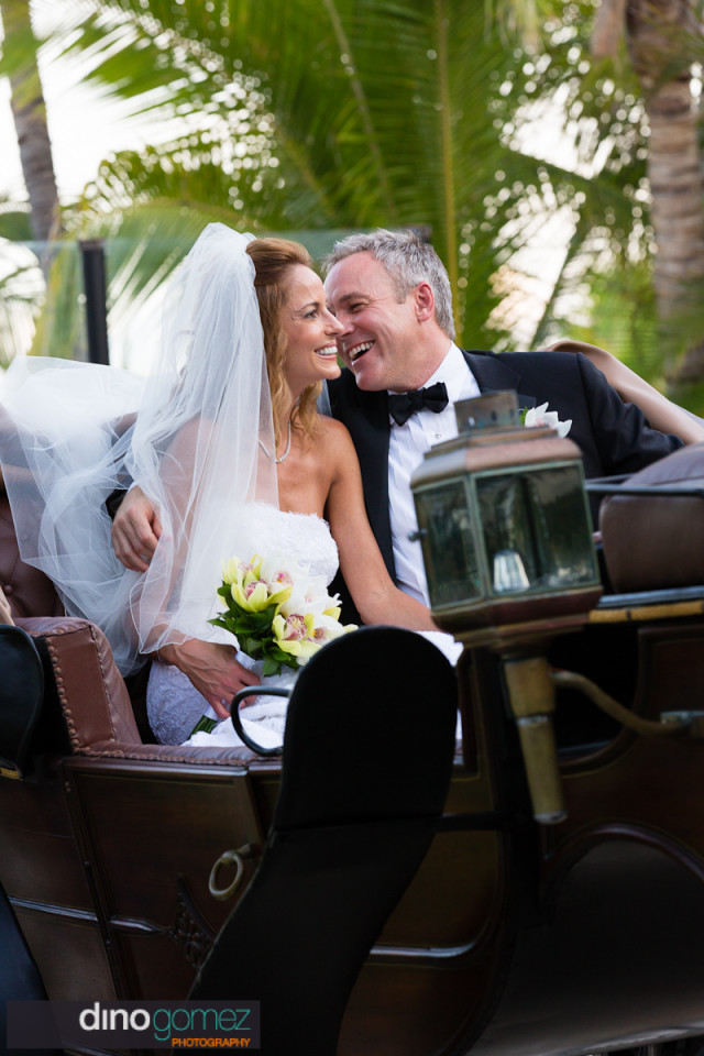 Bride and groom sitting in a carriage after the wedding ceremony