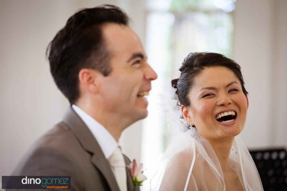 Beautiful shot of the bride and groom laugh during the wedding ceremony by destination wedding photographer Dino Gomez