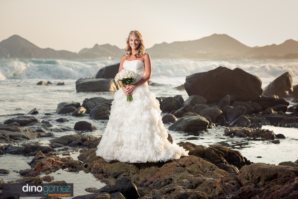 Bride with bouquet of white roses standing on rocks in Mexico