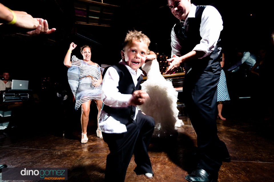 Boy dancing at destination wedding in Mexico with the groom and bride in the background