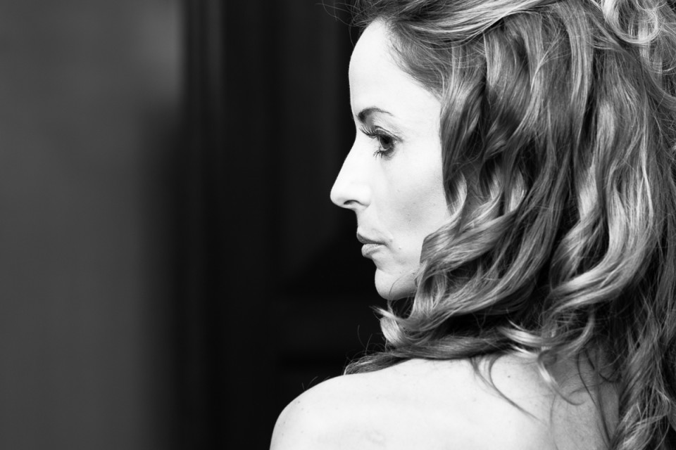 A stunning and atmospheric shot of a gorgeous bride looking over her shoulder