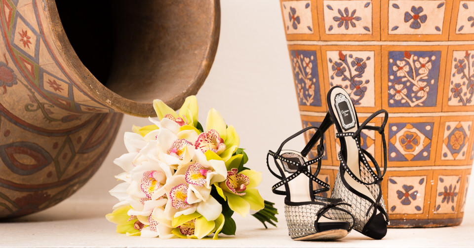 A beautiful floral bouquet laying next to the bride's wedding shoes, both placed in front of two Mexican vases.