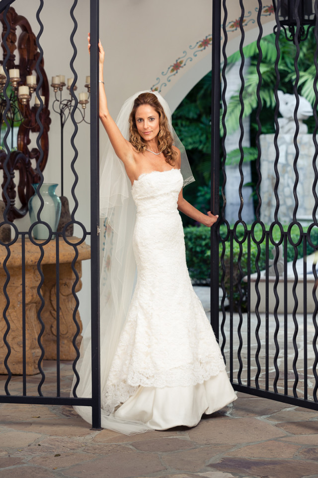 A stunning bride posing next to a set of ornate iron gates in cabo san lucas