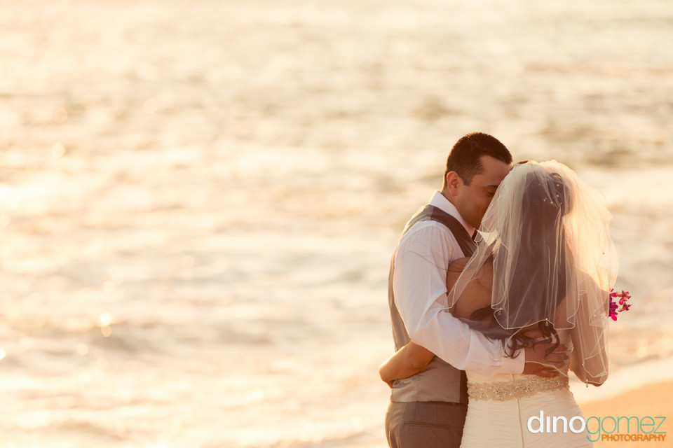 Newlyweds standing face to face on the beach on with their arms around each other on their wedding day