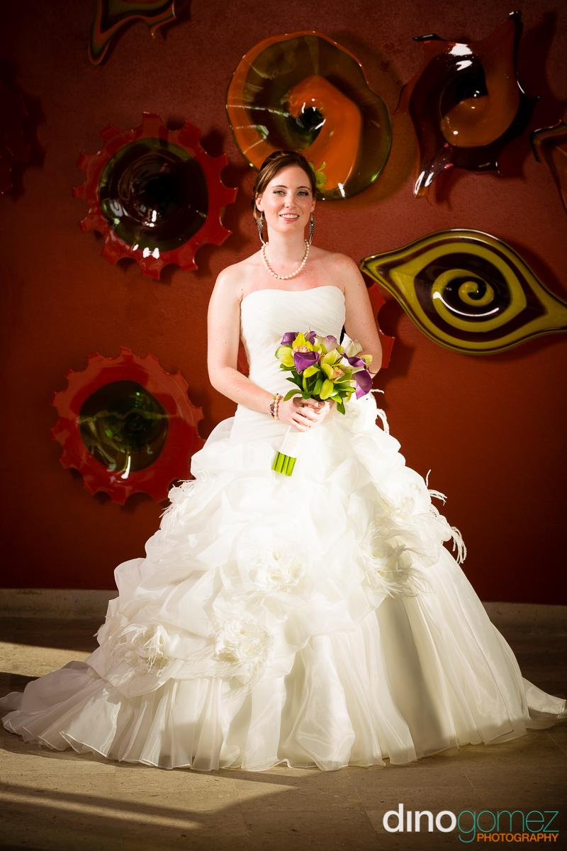 Full-length bridal portrait with a decorative background