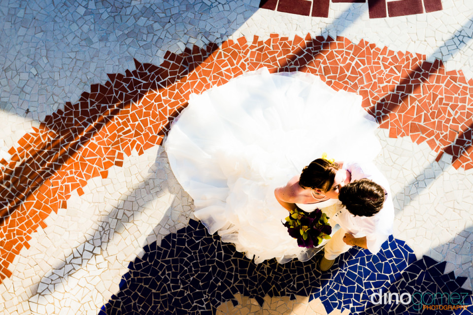 Destination wedding bride and groom kissing on mosaic floor