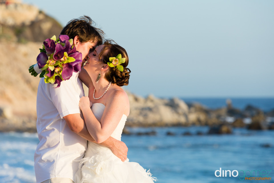 Wedding kissing against a picturesque backdrop on the beach