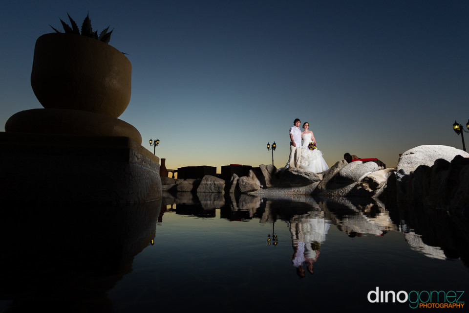 Romantic sunset shot of the newlyweds with their reflection in the water