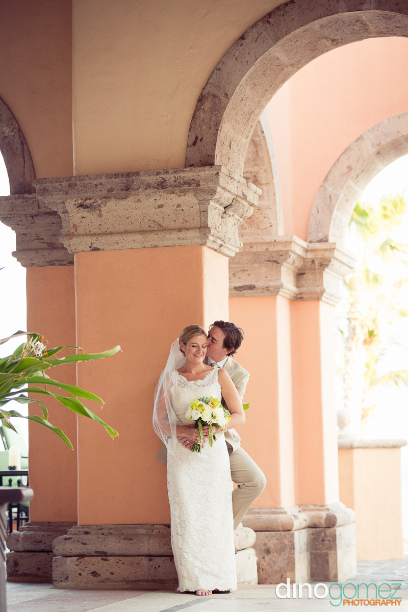 Newlyweds romantic embrace against the column