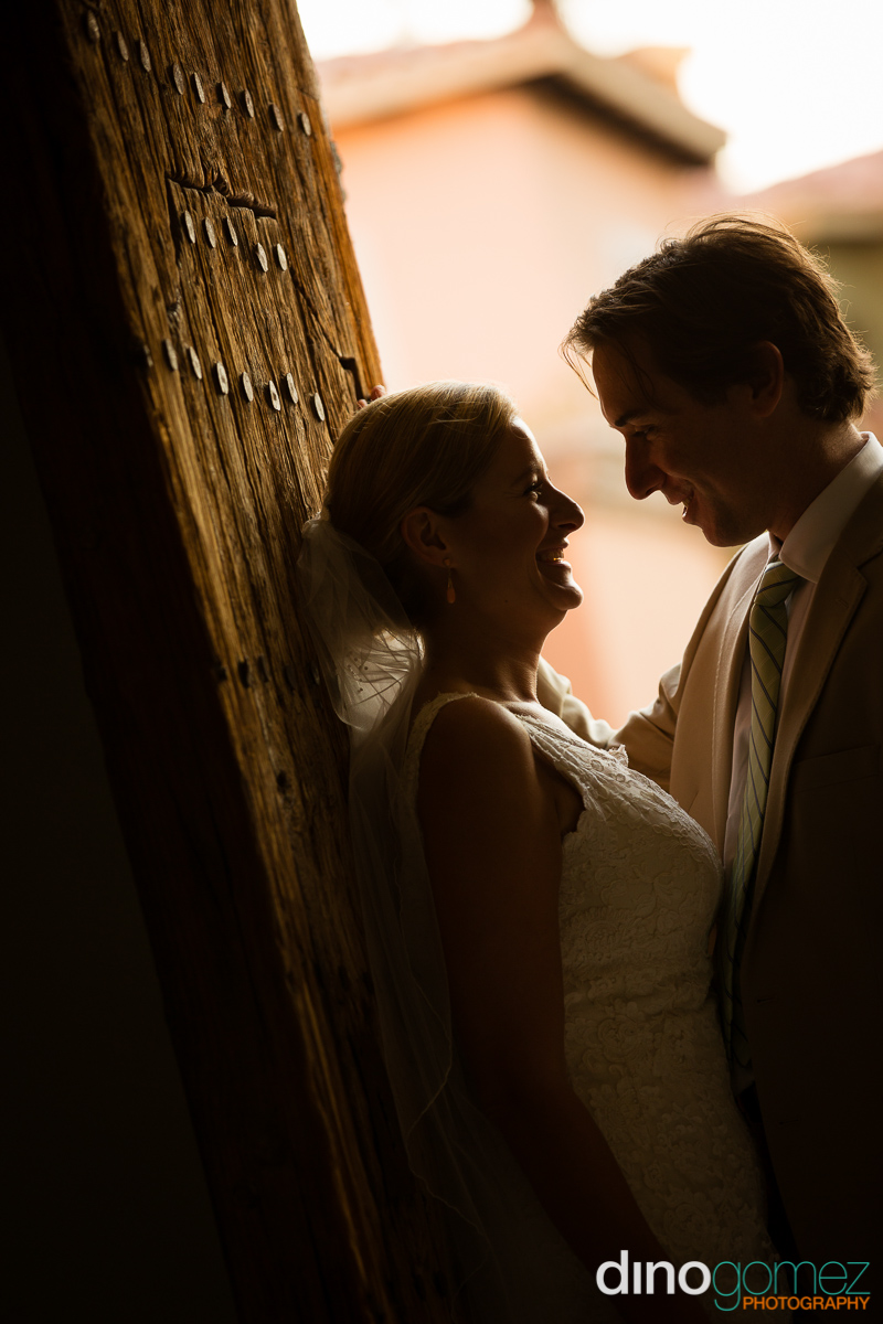 Beautiful shot of the bride smiling and leaning back on a old wooden door as she looks int her grooms eyes