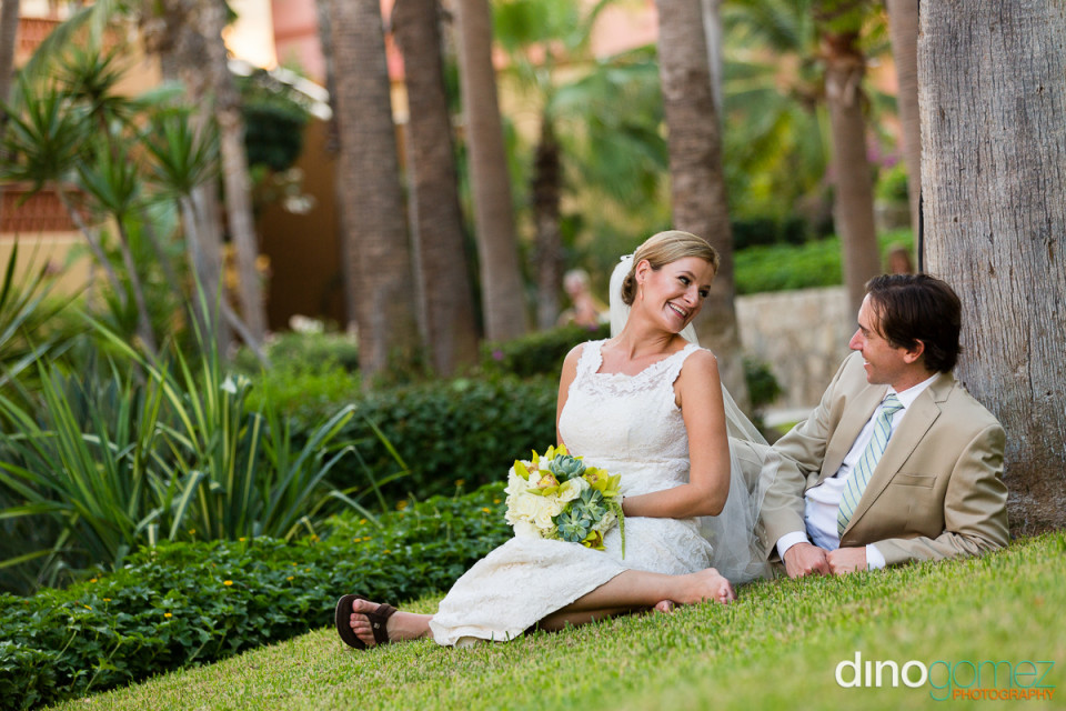 Bride and groom relaxing on the grass after the wedding