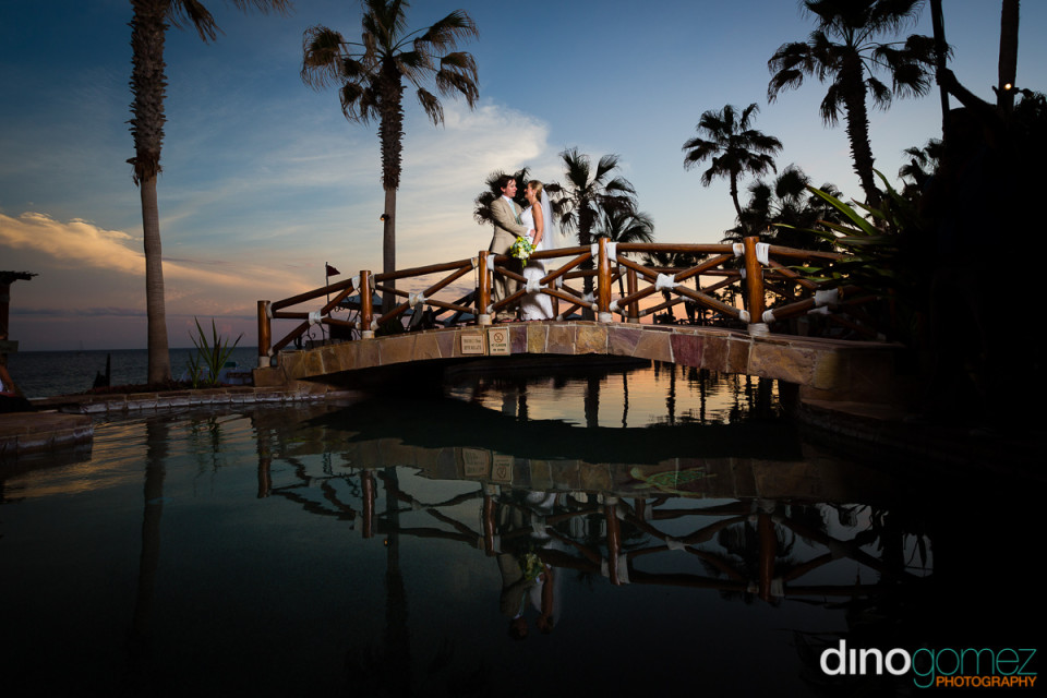 Newlyweds on a bridge over a water feature in Mexico