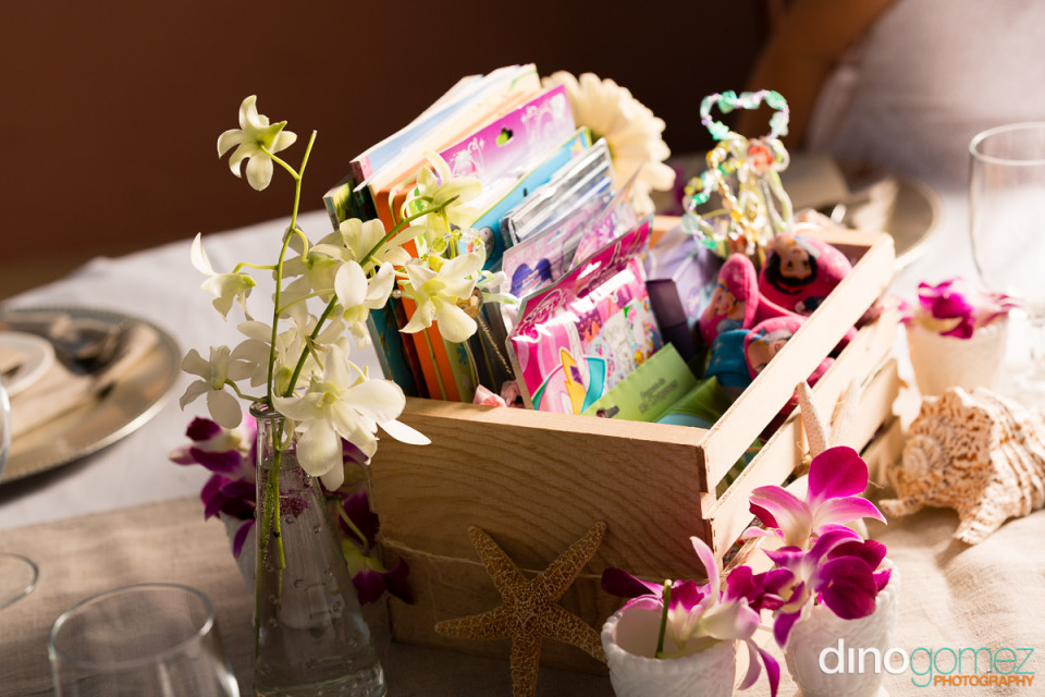 Wooden case display filled with colourful items and surrounded by flowers and shells