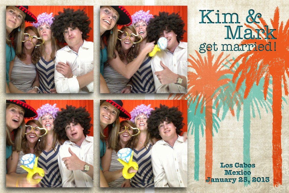 Wedding guests enjoy taking fun photographs in a photo booth provided by Dino Gomez