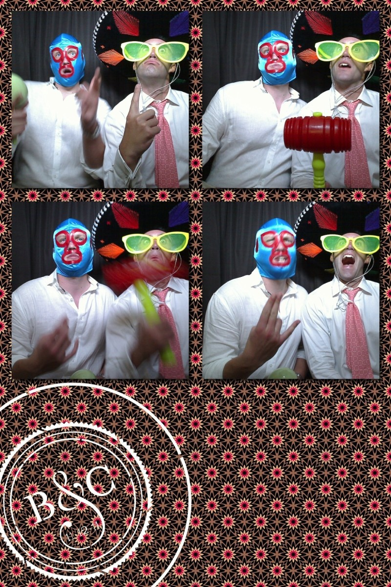 Two male wedding guest use props to make silly photo booth images at a Mexican wedding.
