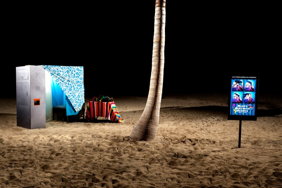 A photo booth set up on a beach at night, taken by Dino Gomez, wedding photographer