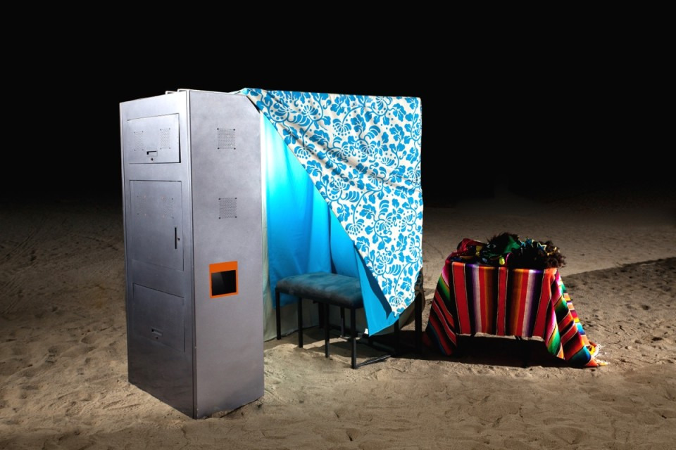 A close up of a photo booth on the beach, with props beside it.