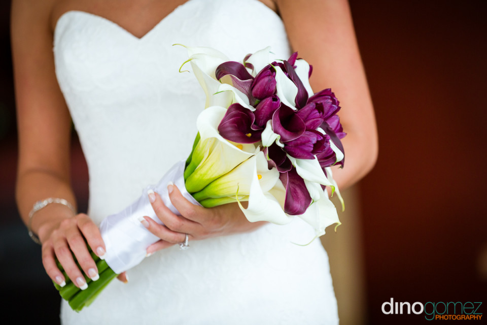 Closeup of bride's hands holding the beautiful wedding bouquet by photographer in Cancun Dino Gomez