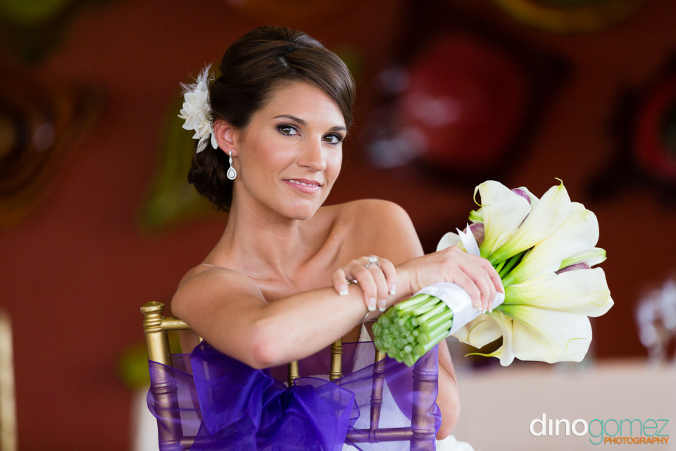Portrait of the bride sitting on chair with her bouquet by destination wedding photographer Dino Gomez
