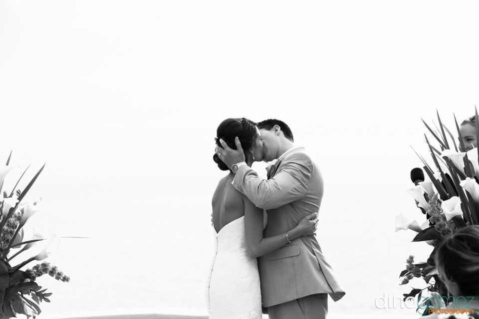 Black and white shot of the bride and groom kissing during their destination wedding ceremony in Mexico